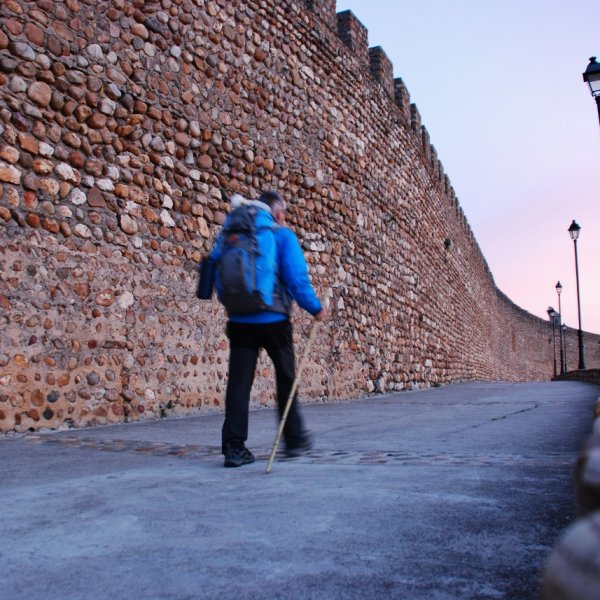 Pilgrim in morning light at ancient walls of Galisteo