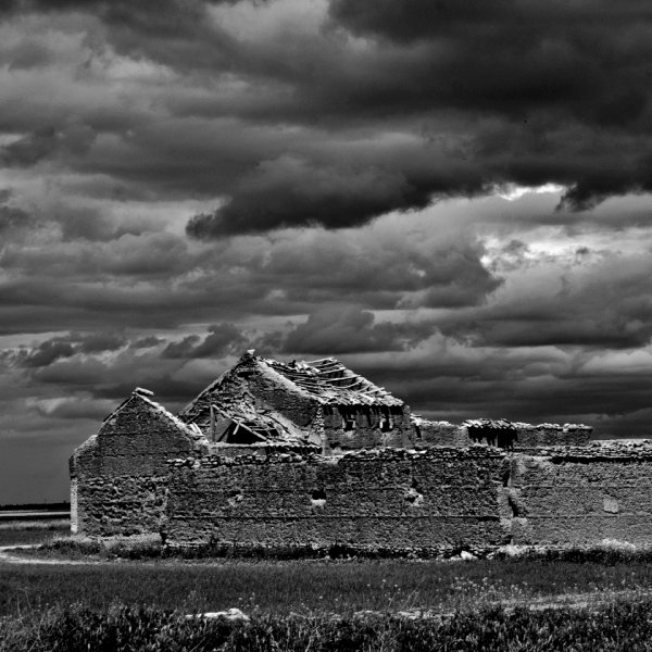 Storm clouds over derelict farm buildings.