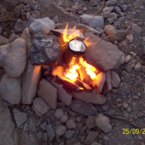 making a fire to cook some water in the desert