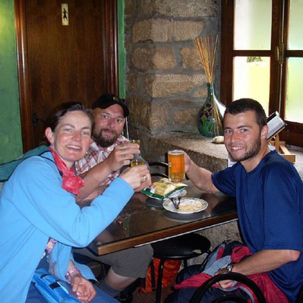 having a drink at the first bar after 100 km to santiago marker